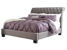 This stately upholstered bed will add great style to your bedroom with a low profile and a grand curving headboard. The headboard features deep diamond tufting and oversized nailhead trim. The bed has turned feet finished in a smooth grey, corresponding with the storage pieces from this collection.