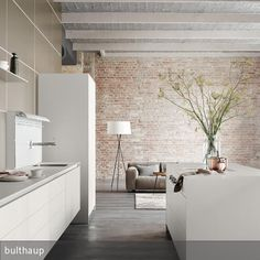 Die schwebende Küchenzeile und die Insel in Laminat führen nahtlos in den Wohnraum über. Tolle Küche in schlichtem, weißen Look von Bulthaup!