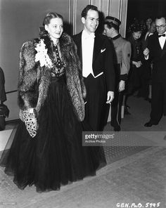 Actress Bette Davis and her husband Harmon Nelson, wearing formal dress, with Davis in a fur coat, attending a movie event, circa 1935
