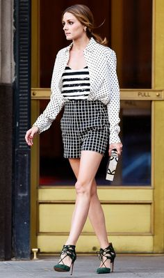 Olivia Palermo boldly mixes several prints in a striped top and polka dotted button-up tucked into windowpane-printed shorts.