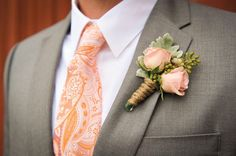 I like the color of the roses in the boutonniere, but the twine is too rustic. Would replace the greenery with hops.