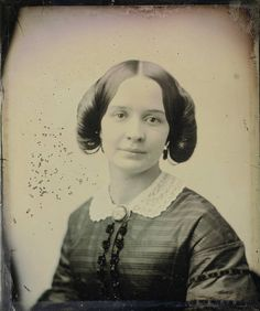 """One popular hairstyles of the Crinoline Period was the """"Victoria Loops."""" The hair was centered parted, and then looped down around the ears into a simple chignon at the back of the head. As you can see in this daguerreotype, the loops began to gain in fullness creating a weird puffiness on the side of the head."""