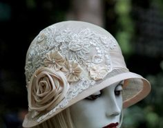 A cottage chic cloche hat for a summer wedding, any special or 20s gala event. The hat is done in several shades of natural sinamay and ivory. The hat is accented with handmade flowers and a sequin and pearl lace appliques. The hat is entirely hand crafted from using a vintage wooden hat block to form the crown, down to the hand formed brim. The accent flowers were made using a antique heirloom ribbon technique and the appliques are all hand sewn into place. The lace appliques may differ…