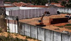 Brazilian security officials worked to complete an improvised wall of metal shipping containers on Sunday inside a prison where rival gangs have clashed in the past week, resulting in the brutal killing of 26 inmates.