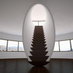 Лестница с деревянными ступеньками, природными цветами из материалов в минималистском интерьере.