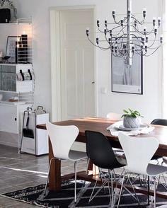 Mustavalkoisia tuoleja puisen ruokapöydän ympärillä