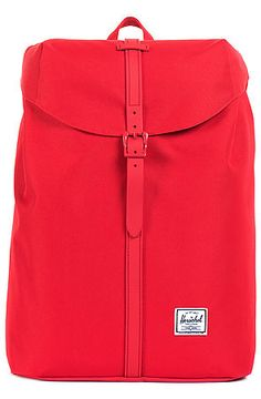 The Post Mid Volume Backpack in Red by Herschel Supply.  This cylindrical bag features a cool, clean design with a single faux-leather strap with magnetic closure and a built-in notebook sleeve. $65