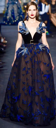 Eli Saab... LOVE the birds, hate the colour and the belt. The underskirt should be like a cloudy sky, and the tulle skirt, a pale blue against which more realistically coloured birds would be flying The bodice could be gunmetal grey.