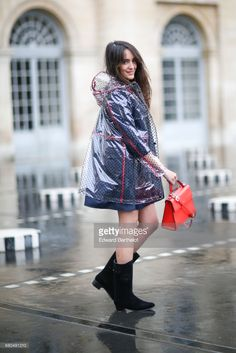 Sarah Benziane, fashion blogger, wears a Zara blue dress, a New Look clear plastic rain coat, an Ali Express red bag, and Chanel boots with flowers, on May 6, 2017 in Paris, France.