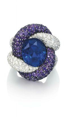A SAPPHIRE, AMETHYST AND DIAMOND RING, BY JAR The entwined diamond and amethyst cords holding an oval-shaped sapphire, to a similarly-set diamond double hoop, mounted in platinum and silver, 1988, ring size 2½ Unsigned