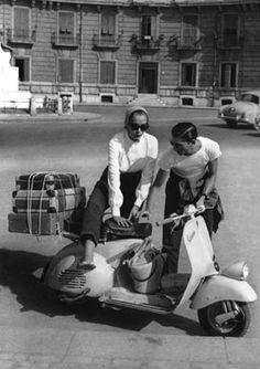 Una giovane coppia è in partenza per le vacanze con la Vespa carica di valigie. 1954