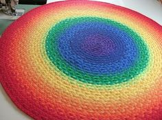 Rug made out of T-shirts. Probably a rag rug. T-shirt fabric would make it really soft.