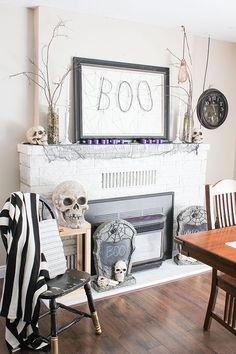 "This Halloween mantel features a black and white palette with a splash of purple. Shonee of Hawthorne & Main DIYed the ""BOO"" on her own DIY mantel art. And the bare branches? Right out of her backyard. See more of her glam Halloween decor on The Home Depot Blog. 