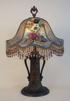 Ornate, Victorian Art Nouveau table lamp holds a Gish shade covered in antique gold metallic lace and and handmade vintage inspired ribbon roses. The colors in this lamp are mysterious and lovely. Victorian Table Lamps, Victorian Furniture, Victorian Decor, Antique Lamps, Vintage Lamps, Vintage Lighting, Antique Gold, Art Nouveau, Objets Antiques