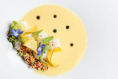 Healthy food from Rouge Tomate. Lightly cooked sea-scallop with a corn couscous, pickled green tomatoes and local peaches, served with a Leche de Tigre sauce.