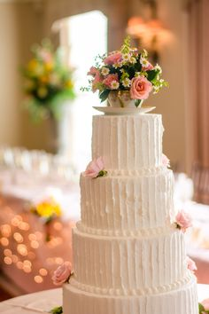 All white wedding cake with chic teacup cake topper