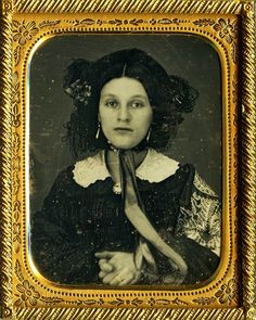 Gorgeous young woman dressed in elaborate mourning attire for her ninth plate daguerreotype likeness. Size: Ninth Plate; Condition: Light wipes and fine permeations/green spots throughout with faint silvering. Resealed with new glass and filmoplast P90. Housing: Nice half brown leatherette case.