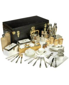 A FINE AND IMPRESSIVE SPECIALLY COMMISSIONED CASED PICNIC SET FOR SIX PERSONS, BY 'AU VOYAGE AUTOMOBILE' OF PARIS, FRENCH, 1905,  black leather-cloth case, with brass handles, locks and catches, the lid opening to reveal wooden compartmentalised tan cloth-lined lift-out interior on two levels, fitted with full compliment of accessories comprising wicker-handled kettle and burner with spirit flask, two large wicker-covered glass drinks bottles, Thermos and Thermidor vacuum flasks, see link