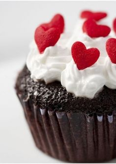 Inspiration for an easy treat for Valentine's Day - top pre-made chocolate cupcakes with whipped cream and candy hearts.