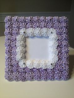 Wood frame covered in lavender and white polka dot fabric yoyos.