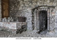 Old stones - stone wall and grated door in abandoned ruins