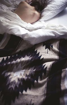 looks so cozy and inviting. soft sheets with rough heavy masculine navajo blanket