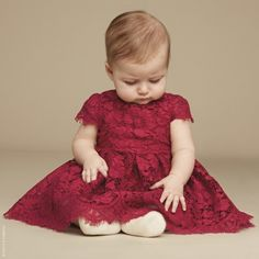 Baby girls adorable raspberry red dress, made in beautiful lace by Dolce & Gabbana. It is high waisted with popper fastenings on the back and has capped sleeves. The full and voluminous skirt is gathered at the waist and has a tulle frill attached to the silky lining beneath. It comes with a pair of silky burgundy knickers, ideal for covering the nappy. Model in first image: Height 67cm Size of dress shown in the photo: 9-12 months