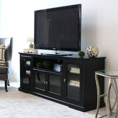Accommodates most TVs up to 70 inches, a perfect fit for any entertainment area. Adjustable shelves with glass-paned doors provide ample storage. Crafted from high-grade MDF and painted in a rich black finish, this stand is sure to please.