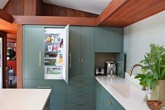 Kitchen Design Idea - 10 Inspirational Examples Of Kitchens With Integrated Fridges // The same calm blue green cabinets used throughout the kitchen also cover this fridge, helping it blend in and hiding it from view.