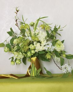 Not into prim bows? Not to worry. Hellebores, green Japanese spray roses, fritillaria, apple blossoms, snowdrops, and double narcissus are softly knotted together with a long, luxurious ribbon. We used velvet Mokuba ribbon #2600, color 13, to complete this relaxed, every-which-way bouquet and kept the stems short and uniformly trimmed.