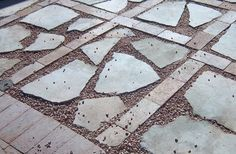 Recycled, broken, concrete chunks used as pavers fill the spaces inside a grid…