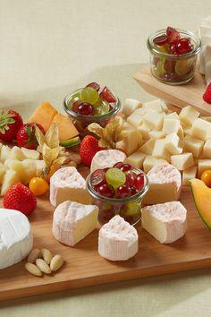 Eine leichte Käseplatte mit verschiedenen Käsesorten und frischem Obst.