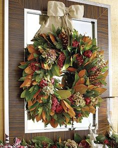 love this magnolia and pomegranate wreath -- composed of wintry elements like fresh fir, magnolia and bay leaves, pepperberries, dried hydrangea, pomegranates and strobus pinecones!  :)