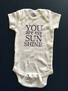 Infant Onsie - You Are My Sunshine.  For the sweet baby that is the sunshine in your world.  Enjoy this onsie for boys or girls.  Color Options are for VINYL color only, on white onsie.   Want this design on a toddler shirt? No problem! We can create that for you today.  All onsies are 100% cotton, name brand, soft white and washable with 2 or 3 easy open snaps. All t-shirts are 100% cotton, name brand, soft color of your choice.