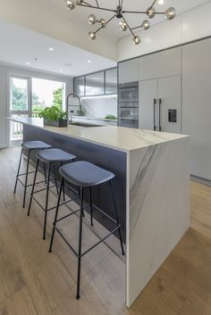The kitchen is a streamlined galley design with a longer island containing the sink. The overhead cupboard section has fluted, smokey glass inserts with blackened steel frames.  The fluted design element has been repeated on the back of the island panels. The soft lines and colour of the benchtop and splashback contrasts the strong vertical design elements of the framed steel and the vertical fluted glass and island panels.A pantry is hidden behind pocket doors and contains a benchtop… Interior, Interior Design Solutions, Contemporary, Vertical Design, Industrial Kitchen Design, Home Decor, Room Decor, Interior Design, Kitchen Design