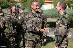 A French Foreign Legion officer (L) from the 2nd Foreign Parachute Regiment coming back from a mission in Afghanistan shakes hand with a colleague upon his arrival at the Raffali military camp near Calvi, on the French Mediterranean island of Corsica, on October 23, 2011. The first 200 French soldiers left Afghanistan four days ago, kickstarting troop withdrawals announced three months ago by Paris as part of NATO plans to wind down its combat mission by 2014.