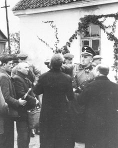 SS Officer forcing Jews to drink from a 'non-kosher' bottle. The act was designed to make the Jew violate his own religious rules and regulations.