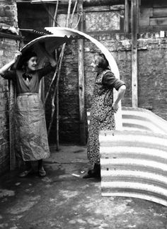 Two women in Islington London try out the height of their new air raid shelter distributed by the government as protection against German bombing...