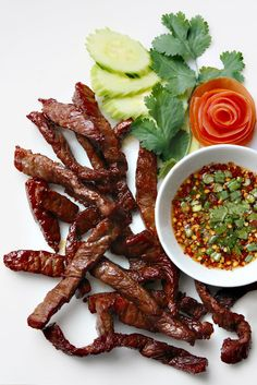 Fried Sun-Dried Beef (Thai Beef Jerky) with Dried Chilli Dipping Sauce from Lers Ros Thai Restaurant, San Francisco: Neua Tod and Jaew (เนื้อแดดเดียวทอดและแจ่ว). I added deep fried lime leafs and sprinkled some deep fried garlic on top. Jerky Recipes, Thai Recipes, Asian Recipes, Beef Recipes, Cooking Recipes, Thai Beef Jerky Recipe, Thai Restaurant, Laos Food, Thai Dishes