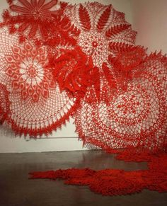 Ashley Blalock | Keeping Up Appearances, Installation 2, San Francisco br/Summer 2011 br/Cotton yarn br/15 x 15 x 10 br/br/ This site-specific installation consists of vibrant red forms nailed to the wall that are actually giant crochet doilies. Although non-threatening in a domestic setting, in the gallery and at this scale the forms overtake the viewer and cover the walls.  br/