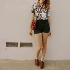 Black and white plaid shirt, black high-waisted button-fly shorts, leather shoes, bag.