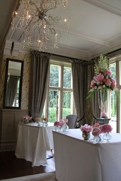 "Inside the ceremony room the scene was set with two of our glorious 'Dahlia"" vases topped with floral magnificence in the form of Delphiniums, Dolce Vita Roses, Hydrangeas, Stocks, Dahlias and Peonies with pale Pink Astilbe and strings of pearls"