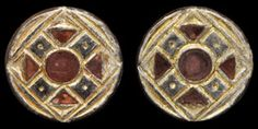 Circa 6th century AD. A pair of silver-gilt disc brooches with lozenge-and-saltire design and central disc; the saltire with central point decoration, the central disc and triangular surround with garnet cloisons; catchplates and pin lugs to the reverse. Silver-gilt and garnet, 9.15 grams total, 26 mm. [2]