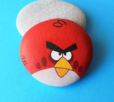 Hand Painted angry bird stone ! A gift idea for your kids, handmade painted stone made by me! Is painted on a smooth sea stone which i have collected from a beach on a Greek island. Is painted with fine art quality acrylic colors and very small brushes for the detail , is signed on the back and covert with strong glossy acrylic stone varnish for protection. Dimensions approximately : Height : 5.2 cm ( 2 in ) Width : 5.8 cm ( 2.3 in ) Your art works will arrive carefully packaged…
