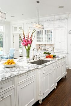 Love the chandeliers, marble, and cabinetry.