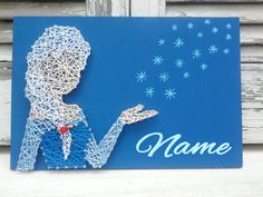 This wooden decoration, Elsa From the animation movie Frozen, made from string and nails on a blue painted wooden piece (0,20x0,30m), is the perfect hanging decoration for your home. I can hand paint any name you want at the bottom right corner.  Any of the signs take 4-5 days to make. After that they will be shipped immediately.  -Any color or size available upon request.