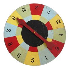 Circa 1930 solid wood game wheel with vibrant and graphic multi colored squares, wood arrow indicator, original painted surface.