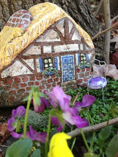 Painted rock house in fairy garden.