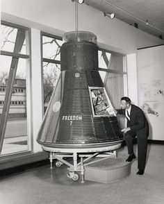 "Astronaut Alan Shepard peers inside the Mercury ""'Freedom 7""' spacecraft which he flew on May 5, 1961. The spacecraft was presented to the Smithsonian on October 23, 1961, and placed on display in the Aircraft Building (aka Quonset Hut) in the South Yard by the Smithsonian Castle. Source: Smithsonian Institution Archives"