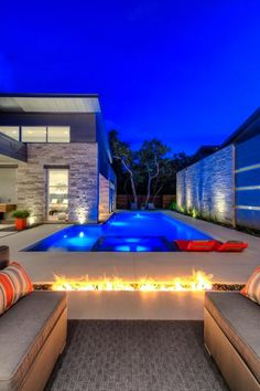 JMS Architects created a modern outdoor area perfect for relaxing and entertaining. A linear fire pit runs parallel to a sleek swimming pool, with deck and patio areas offering plenty of seating options.